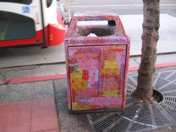 This trash can at a bus stop was brightly decorated by a street artist.