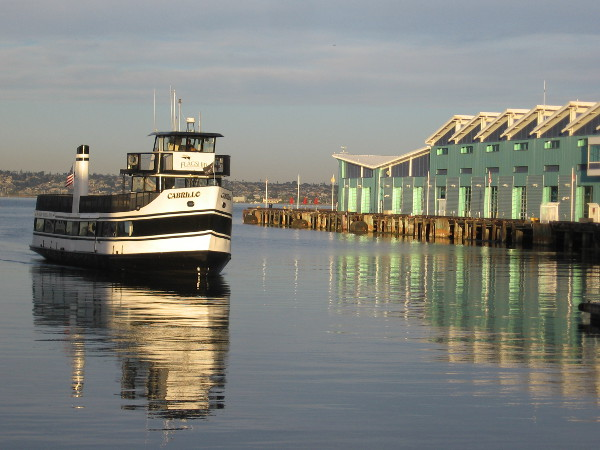 Flagship's ferry ship Cabrillo arrives at the Embarcadero. Emerald light on the bay is reflected from the Port Pavilion on Broadway Pier.