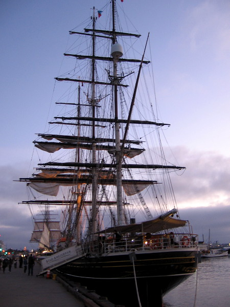 Photo of stern of Stad Amsterdam as the sun is setting behind a bank of clouds. The sails of Star of India, pride of the Maritime Museum of San Diego, can be seen in the distance.