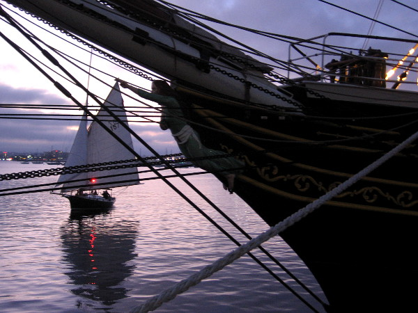 A sailboat cruises on gleaming San Diego Bay past the figurehead of Stad Amsterdam.