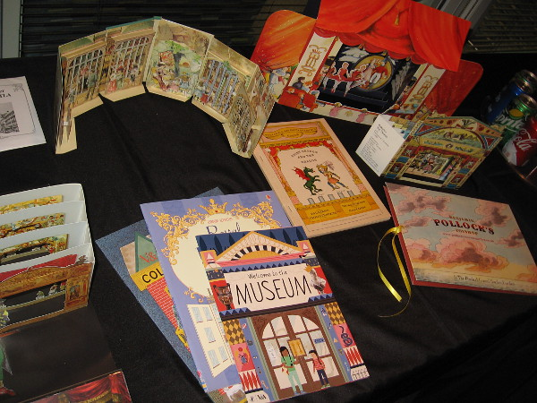 Objects on display include books, posters and materials to craft paper theaters.