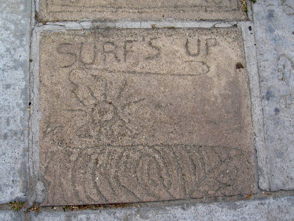 Surf's up. One of many underfoot messages in panels of concrete near the corner of Avenida de la Playa and Paseo del Ocaso.