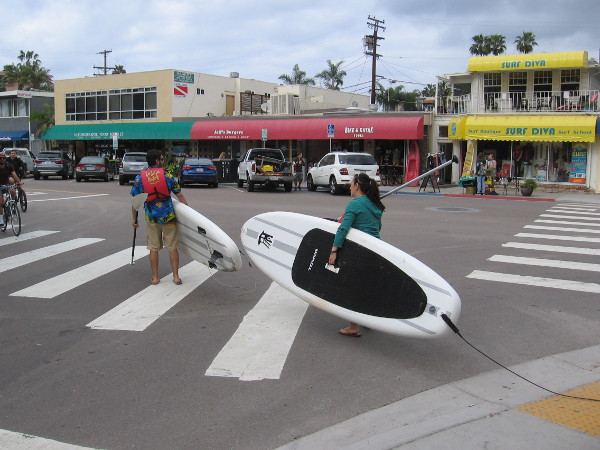 Carrying paddleboards west toward the nearby beach. Kayaking in the Pacific Ocean off La Jolla is also very popular.