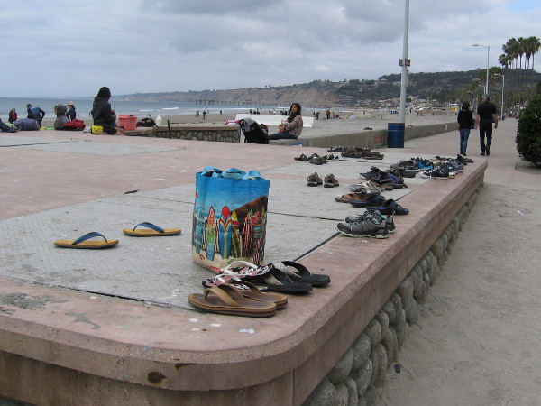 Beachgoers have left some flip-flops and shoes at the west end of Avenida de la Playa. Sand feels good under bare toes.