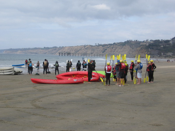 A group of kayakers receives instruction before heading out onto the Pacific Ocean.