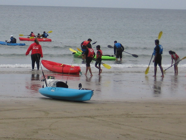 People enter the Pacific Ocean with colorful kayaks and paddles.