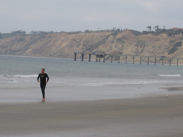Running along the beach at La Jolla Shores. To the north one can see Ellen Browning Scripps Memorial Pier, and beyond the high sandstone cliffs of Black's Beach.
