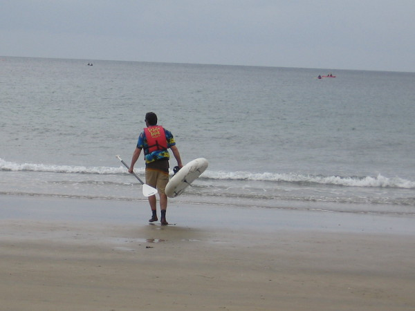 A man carries his kayak across the sand toward the water. It's an overcast winter day, but very pleasant.