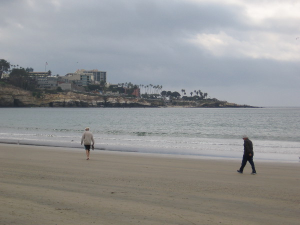 Two people walking south along the smooth beach. La Jolla Cove can be seen across La Jolla Bay.