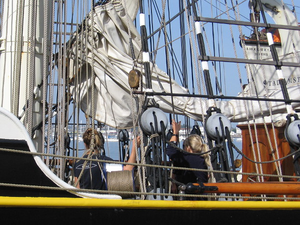 Members of the Stad Amsterdam crew work together to manipulate a sail.