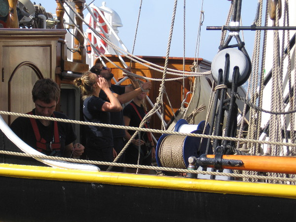 Hauling a rope that is attached to a canvas sail high above.