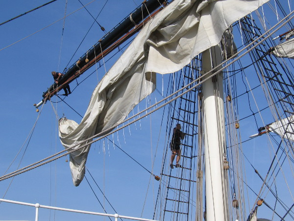 Crewmembers take to the ship's rigging to do some work.