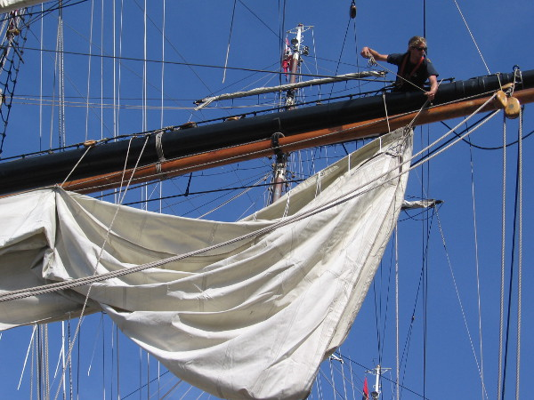 Out on a yard unfurling a heavy sail.
