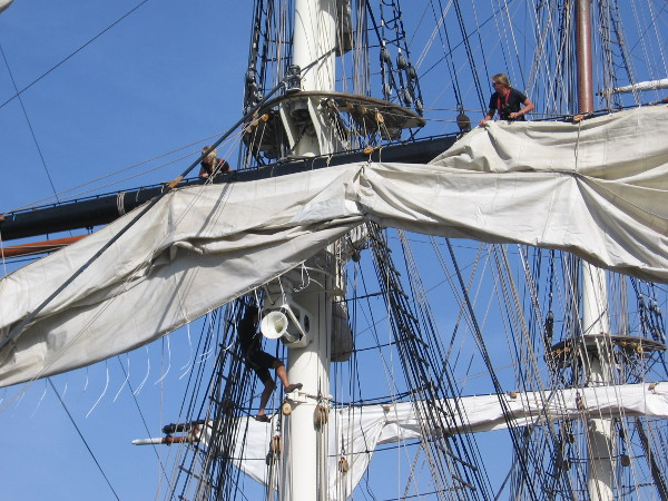 Crew members wrestle with a sail.