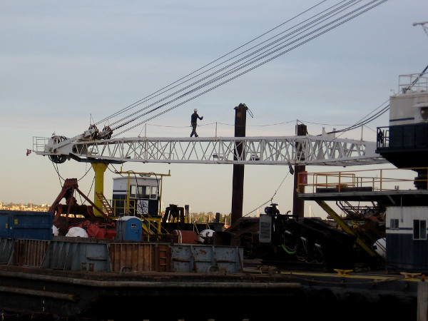 Man walks across a crane that is being used to demolish the old Anthony's Fish Grotto.