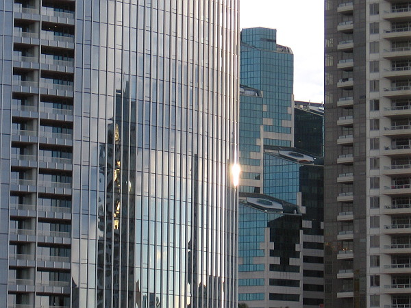 Gleaming light on several downtown skyscrapers, including Pacific Gate and Emerald Plaza.