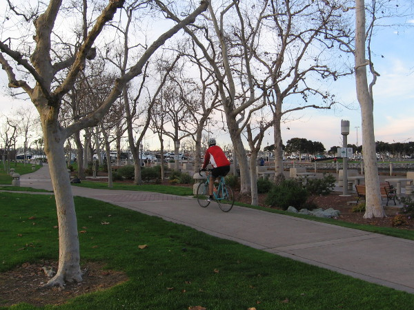 Riding a bike along a path near the USS Midway.
