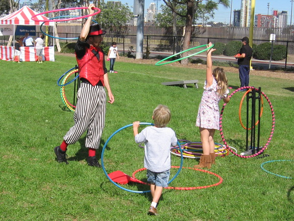 The circus juggler and some kids play with colorful hula hoops.
