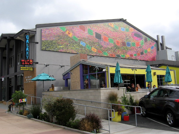Mural on west side of Galaxy Taco includes images of colorful Mexican papel picado.