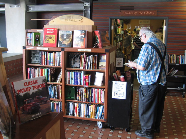 Someone pauses near the front desk of San Diego's Central Library to browse a few of the many incredible used books!