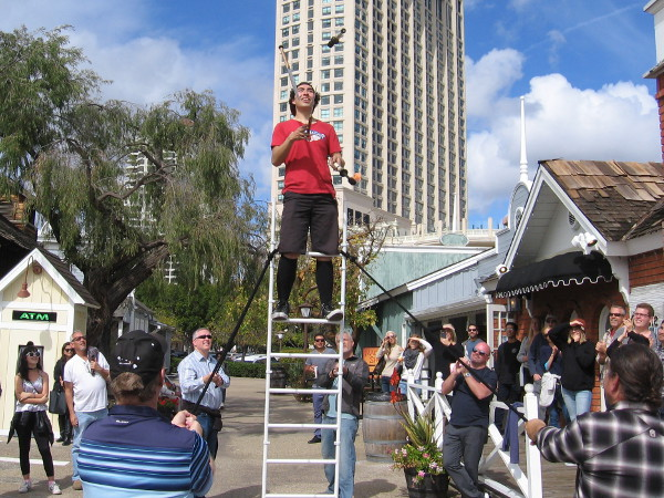 Sam Malcolm, a juggling comedian from Denver, Colorado, performs high atop a ladder during the Seaport Village Spring Busker Festival!