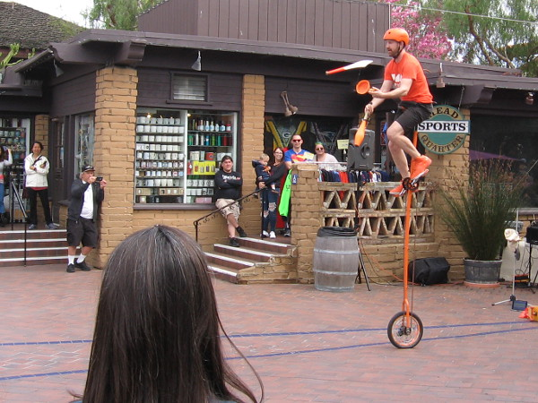 More juggling. This time atop a super tall unicycle.