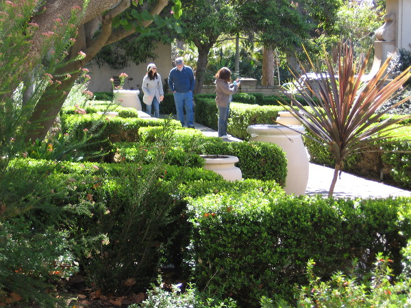Visitors enjoy the quiet, sunlit beauty of the Alcazar Garden.