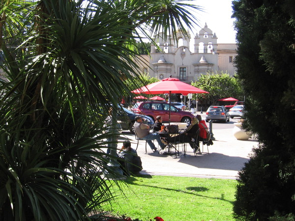 People relax at a table under a red umbrella in the Plaza de Panama. The House of Charm rises in the background.