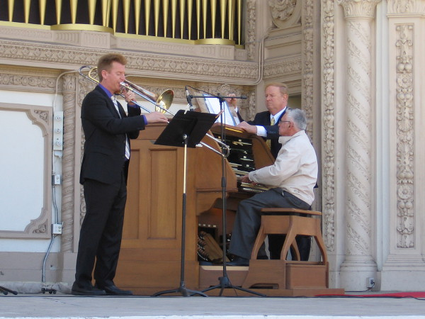 Trombonist Eric Starr joins Robert Plimpton on the stage of the Spreckels Organ Pavilion. They are practicing before the Sunday afternoon concert.