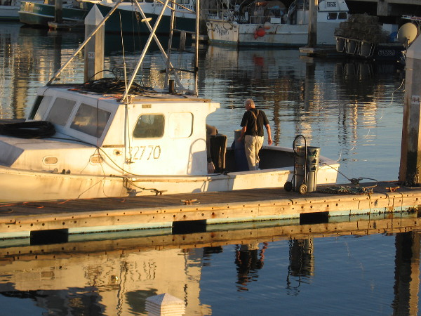 A reflection of man and fishing boat in Tuna Harbor.
