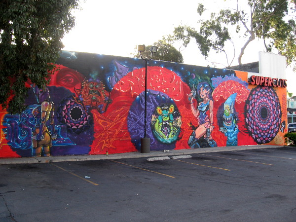 A cool mural on the Supercuts building in North Park depicts sexy lady space warriors and wacky, evil aliens!