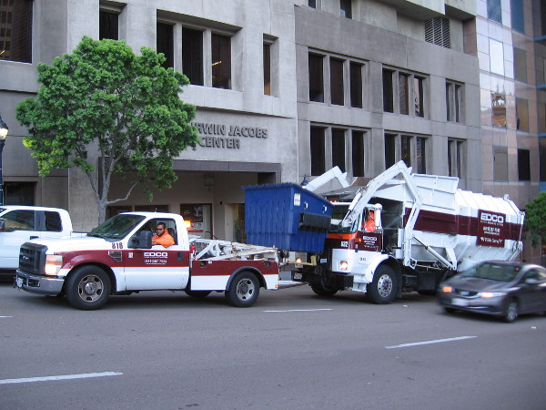 Garbage truck lifts dumpster in front of the San Diego Symphony's Joan and Irwin Jacobs Music Center.