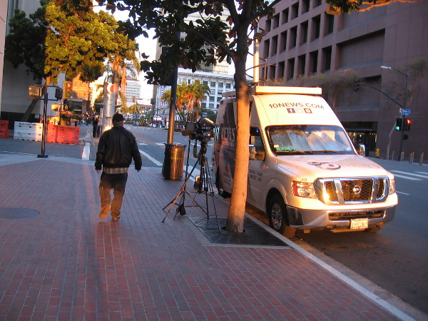 A TV news van is parked by the Hall of Justice one evening.