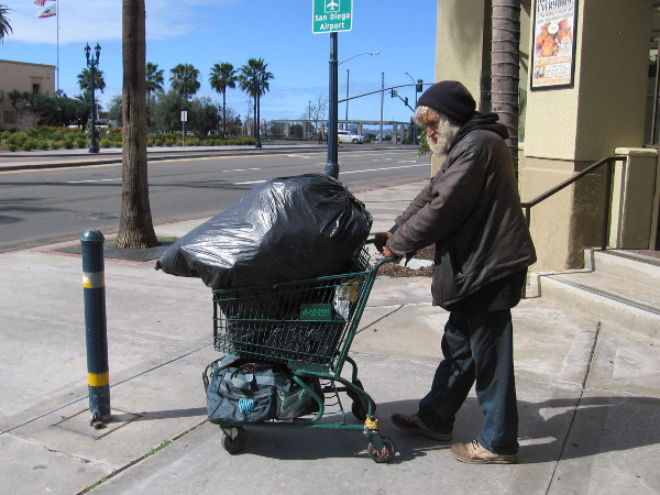 Homeless man walks through life with his stuff.
