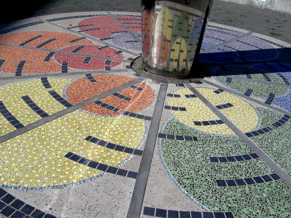 Colorful tiles radiate at the base of the rotating, wind-driven blades.