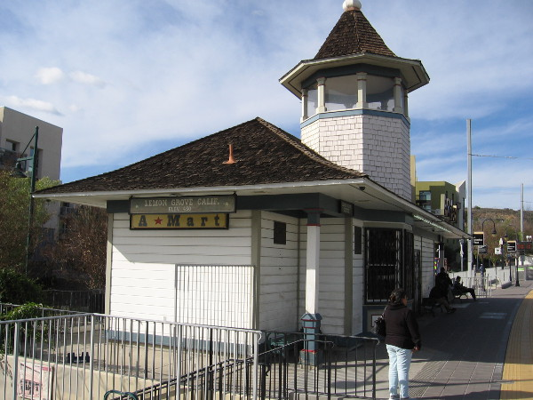 People wait for an Orange Line trolley at the Lemon Grove station. The original structure had an open cupola so the depot agent could wave signal flags at oncoming trains.