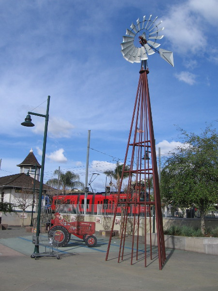 A farm's windmill and tractor are reminders of an agricultural past. They stand in a public park beside the Lemon Grove Trolley Depot.