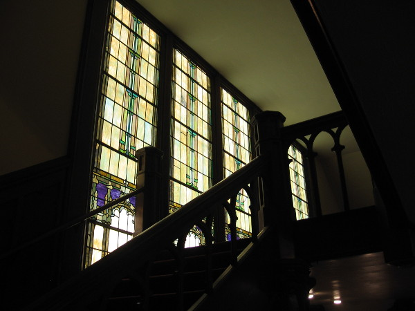 Heading up some handsome stairs near colorful stained glass. We will emerge on the sanctuary's balcony.