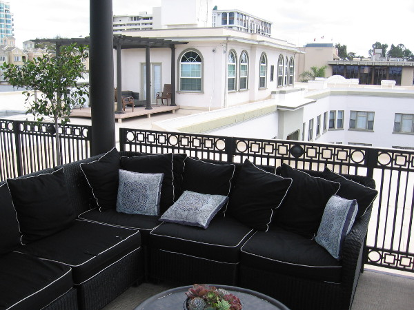 The building's penthouse apartments are beyond this comfy outdoor sofa.