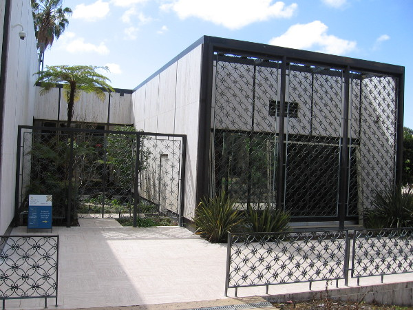 Fences enclosing a small garden and sections of the museum seem like airy lacework. The building's white travertine reflects San Diego's sunlight.