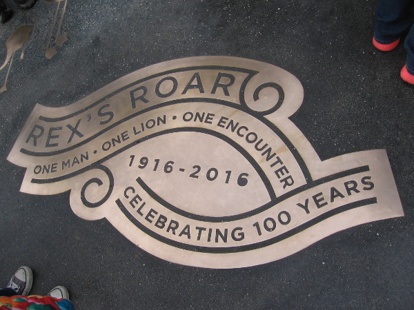 Inlaid near the public art's base is the shiny inscription Rex's Roar. One Man - One Lion - One Encounter. 1916-2016. Celebrating 100 Years.