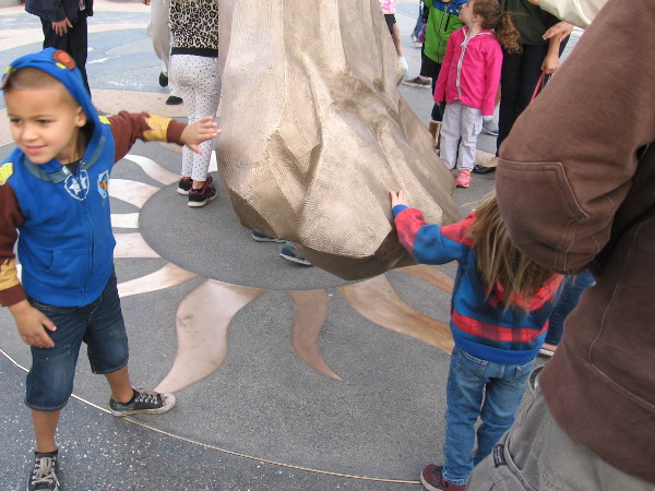 Kids rush up to touch the golden sculpture!
