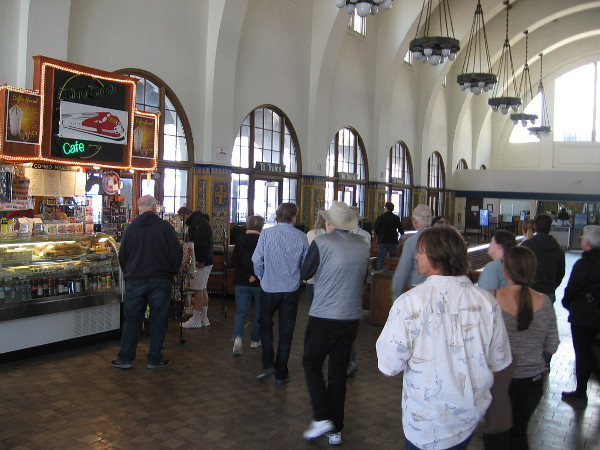 Amtrak passengers move through the Santa Fe Depot's large waiting room. The building's architecture is in the Mission Revival style with Spanish Colonial Revival influences.