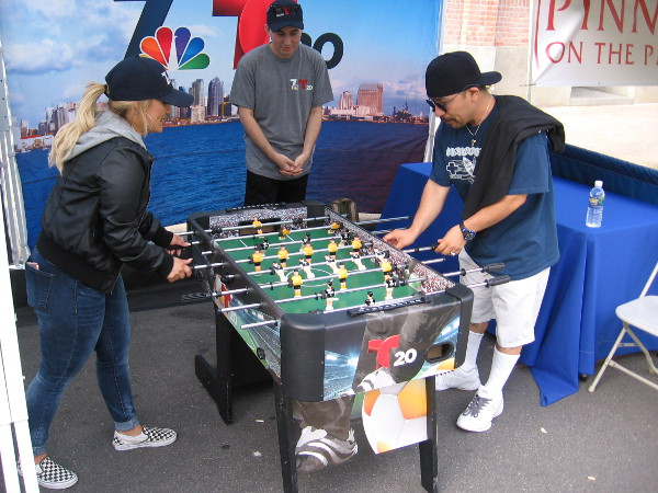 These guys were playing table soccer at a fun TV station's booth.