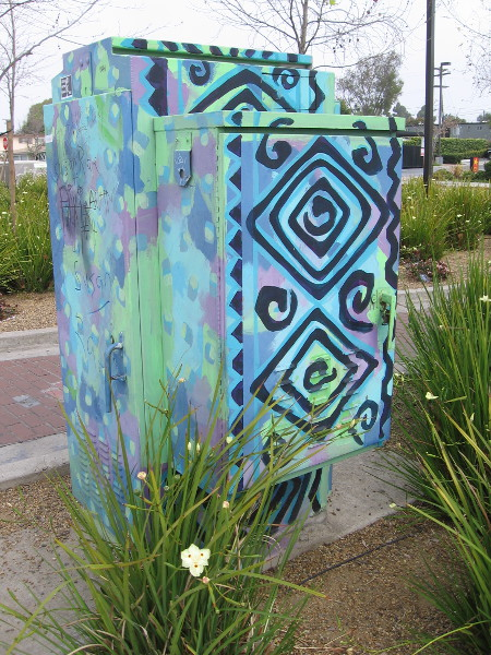 A nearby utility box is painted with colorful designs.