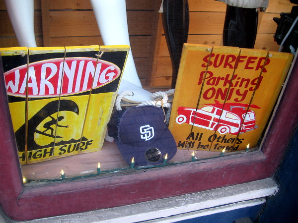 Two humorous surfing signs in the window of San Diego Trading Company Gaslamp.
