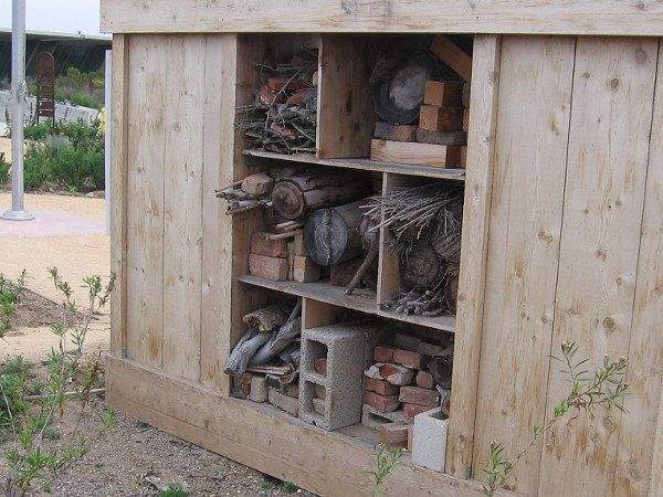 The rear of this bee condo! Holes have been drilled in a variety of materials, including logs, lumber and bricks.