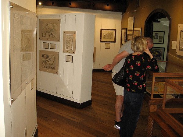 Visitors look at an amazing collection of historic maps at the Map and Atlas Museum of La Jolla.
