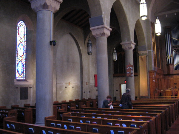 People have quietly entered the sacred place. The gray interior walls allow the stained glass lancet windows, created by Judson Studios in Pasadena, to fill the eyes of worshipers.