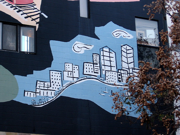 A clean, beautiful city on the water, painted on the side of a building in Little Italy.